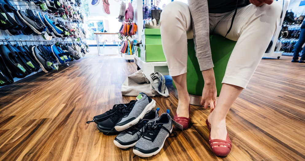 Customer trying on several shoes-1