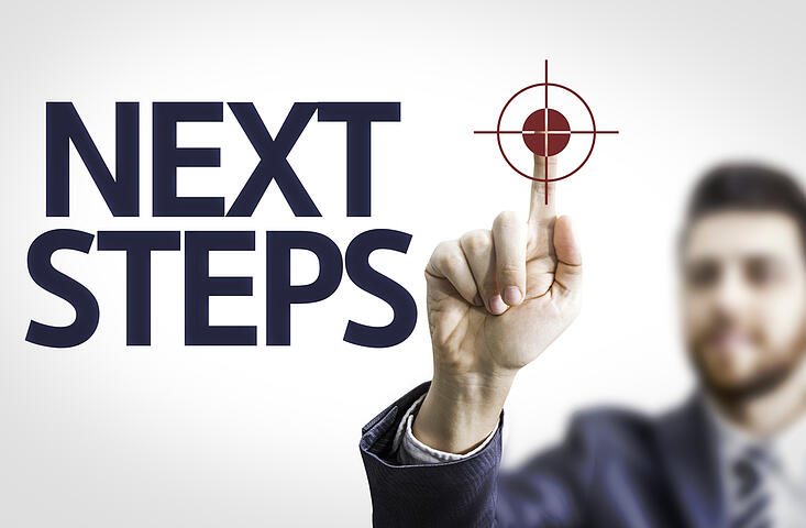 Business man pointing to transparent board with text Next Steps