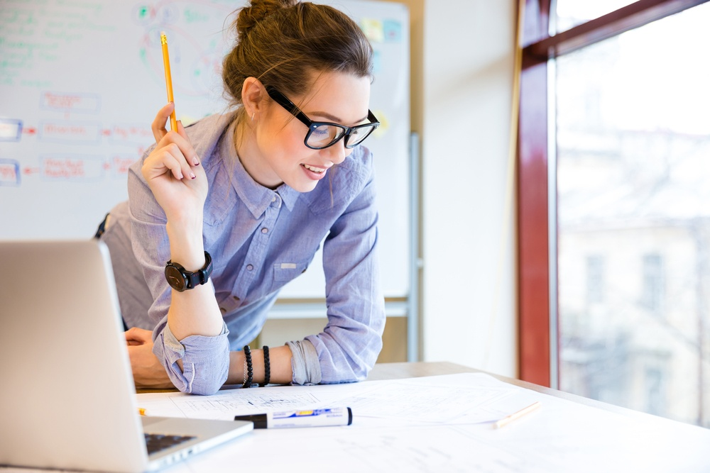 Happy young woman in glasses standing near the window in office and working with blueprint .jpeg